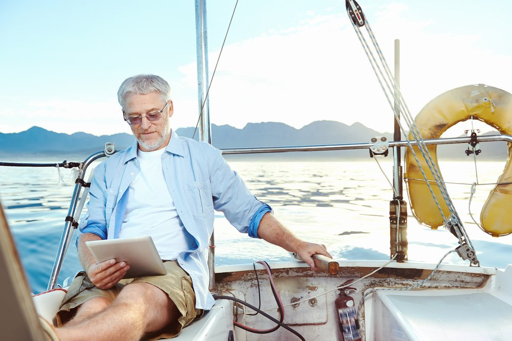 Old man reading on his yacht